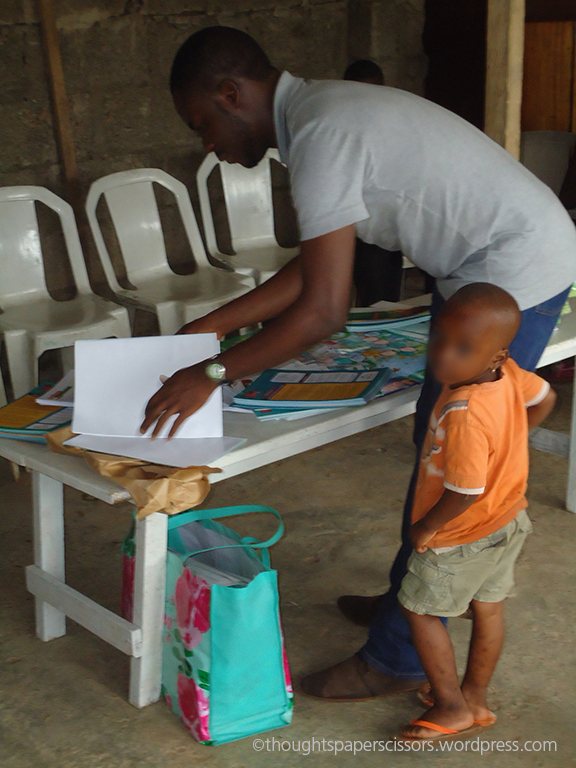 BJ setting up the resources for money game with one very friendly child at the orphanage